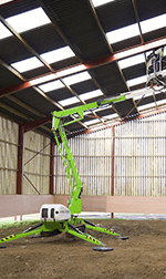 green spider lift in a large barn